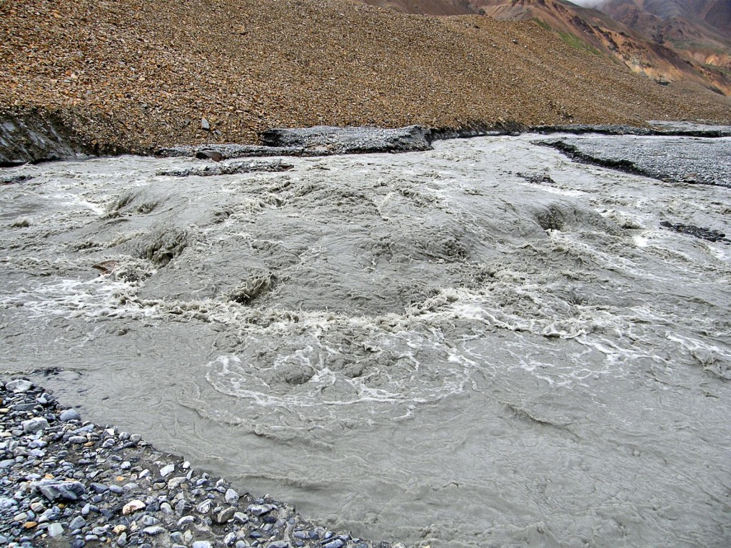 The outlet stream suddenly appears from under the glacier as a bubbling spring.